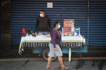 Una mujer camina frente a un vendedor ambulante, ambos con mascarilla de protección, este lunes, en Sao Paulo (Brasil).