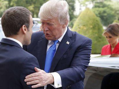 El presidente francés, Emmanuel Macron (izquierda), recibe al estadounidense, Donald Trump, con la primera dama estadounidense Melania al fondo.