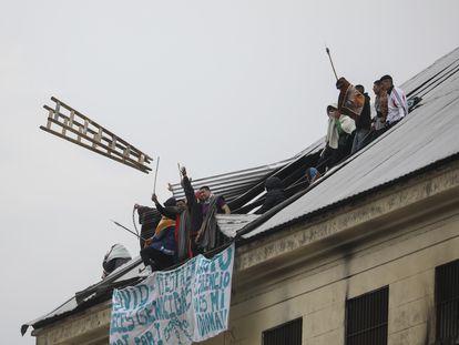 Un grupo de presos amotinados arroja una escalera desde el techo de la cárcel federal de Devoto, en la ciudad de Buenos Aires, el 24 de abril.