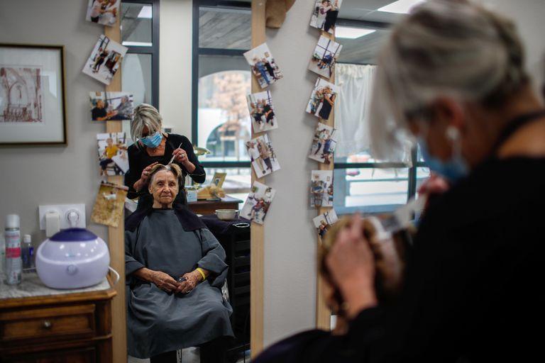 Una peluquera atiende a una paciente afectada por el alzhéimer en una residencia francesa.