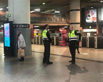 Dos vigilantes de Cercanías sin mascarilla, este lunes a mediodía en la estación de Atocha de Madrid. L. F.