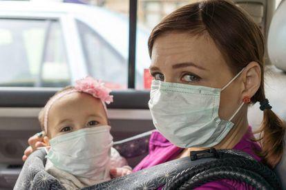 Una madre y su bebé con mascarilla en un coche.