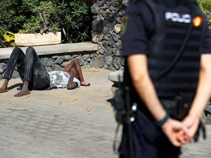 Un hombre yace en el suelo tras llegar en patera a la playa de Maspalomas, en el sur de Gran Canaria el pasado 1 de noviembre.