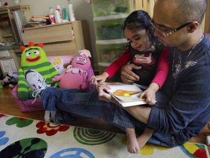 Christopher Astacio lee con su hija, Cristina de dos años, diagnosticada de autismo.