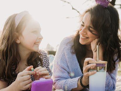Madre e hija charlan en un porche.