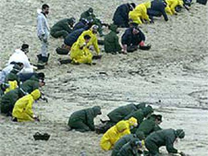 Grupos de militares limpian la playa de Ancoradoiro, en Muros (A Coruña).