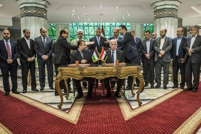 Azzam al-Ahmad (en la mesa, a la derecha), representante de Fatah, y  Salah al-Aruri  (izquierda), líder de Hamas, firman la reconciliación en el Cairo, este jueves