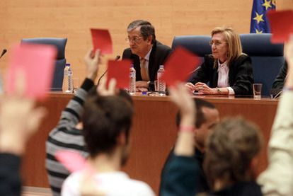 Varios estudiantes muestran tarjetas rojas a Rosa Díez, sentada junto al profesor  Rafael Calduch.