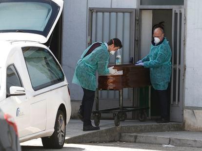 Dos funerarios trasladan un féretro en el hospital Ramón y Cajal.