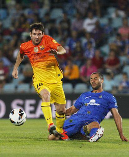 Lacen trata de derribar a Messi durante el partido.