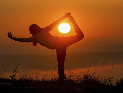 Una mujer hace yoga al amanecer.