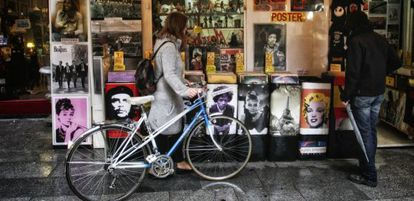 Una chica ojea discos de vinilo junto a su vieja bicicleta.