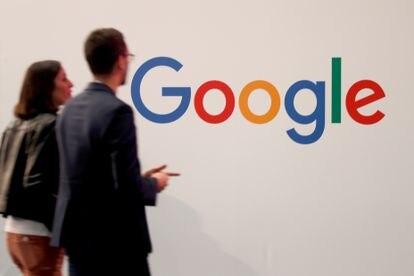 Dos personas pasan ante el logotipo de Google en un encuentro de empresas tecnológicas en París.