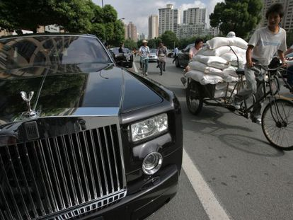 Un ciclista que acarrea sacos pasa junto a un Rolls-Royce en Shanghái.