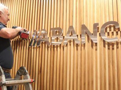 Un obrero coloca el nuevo logotipo en un edificio de la entidad en Santiago