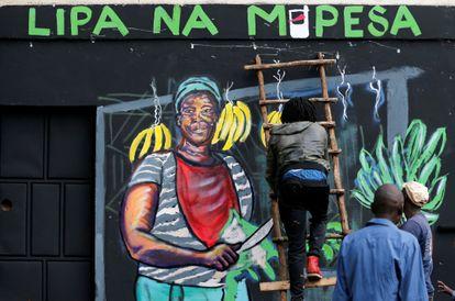 Un artista trabaja en un mural que aboga por los pagos sin dinero en efectivo de los teléfonos móviles M-Pesa como medida contra la propagación de la covid-19 en Nairobi, Kenya, el pasado 19 de abril.