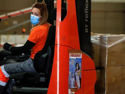 Una trabajadora con mascarilla en una empresa logística.