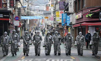 Soldados surcoreanos desinfectan una calle de Seúl.