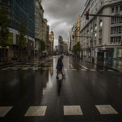 La expansión del virus por nuestro país y la declaración del estado de alarma el 14 de marzo dejaron un panorama nunca visto en nuestra democracia: ciudades casi sin gente ni actividad. En la imagen, una mujer cruza un paso de peatones en la Gran Vía de Madrid, el pasado 23 de marzo.
