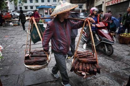 Un vendedor ambulante trabaja en la ciudad antigua de Fenghuang en Xiangxi, China central.