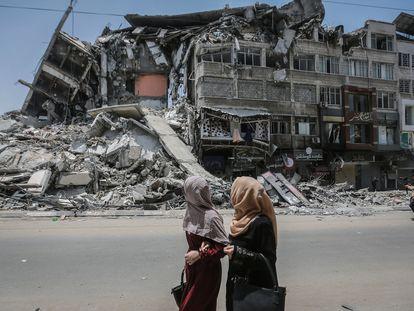 Varias personas pasan frente a un edificio destruido por los bombardeos en Gaza.