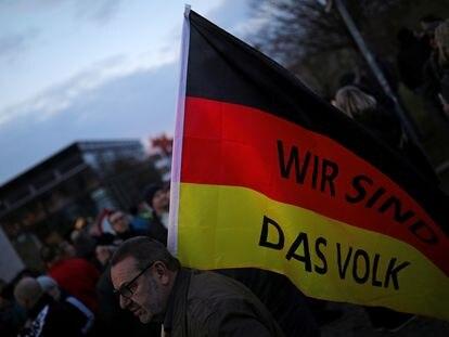"""Un simpatizante de Alternativa para Alemania (AfD) en Erfurt porta una bandera alemana en la que se lee: """"Nosotros somos el pueblo"""", el pasado marzo."""