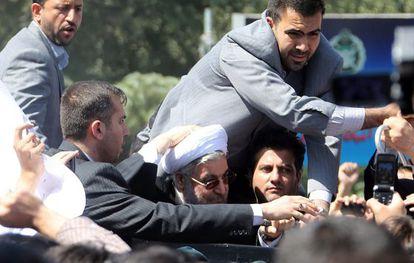 Rohaní, rodeado de sus guardaespaldas a la llegada a Irán.