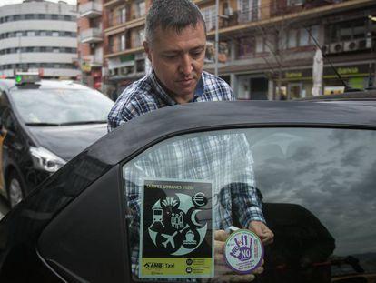 Un taxista coloca en su automóvil una pegatina de la campaña violeta.