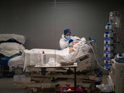 Una sanitaria atiende a un paciente en el hospital de emergencias Isabel Zendal.