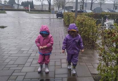 Maia y Milena, vestidas con el traje de lluvia y las botas de agua, vuelven al colegio en Dinamarca.