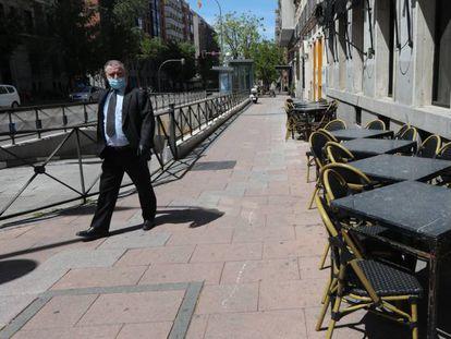 Un hombre con mascarilla pasa junto a una terraza cerrada de un bar en Madrid.