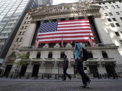 Dos personas pasan este viernes frente a la Bolsa de Nueva York.
