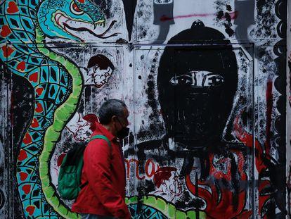 """Una persona pasa frente a un grafiti alusivo al Escuadrón Zapatista """"La Extemporánea"""" en Ciudad de México."""