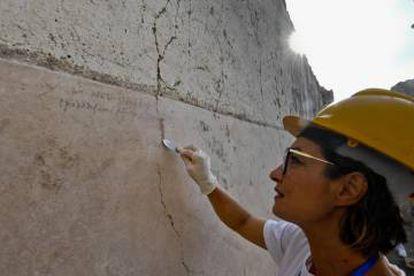 Una arqueóloga muestra la inscripción hallada.