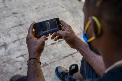 El haitiano Enold Desroches sigue en su celular la toma de posesión de Biden.