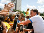 Brazilian President Jair Bolsonaro greets supporters in front of the Planalto Palace, after a protest against the National Congress and the Supreme Court, in Brasilia, on March 15, 2020. (Photo by Sergio LIMA / AFP)