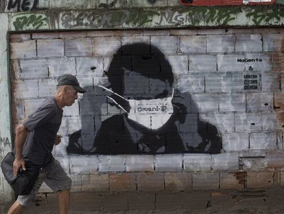 Un ciudadano pasa ante un grafiti del presidente Bolsonaro.