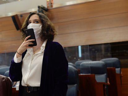 La presidenta de la Comunidad de Madrid, Isabel Díaz Ayuso (d), manda un mensaje con su teléfono a su llegada a la sesión del pleno de la Asamblea del pasado 17 de diciembre.