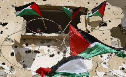 Dos jóvenes ondean banderas palestinas en Rafah (Gaza) en una protesta para pedir a Egipto que suministre electricidad y combustible a la Franja.