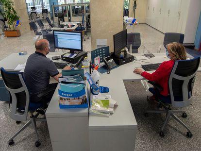 Dos empleados en su puesto de trabajo de la Oficina de Hacienda de la Calle de Guzmán el Bueno, el 27 de julio en Madrid.