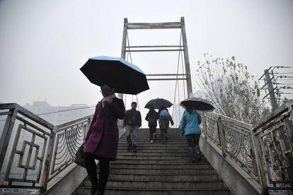 Algunas personas pasan delante de un edificio envuelto en una severa contaminación del aire en Harbin, China.