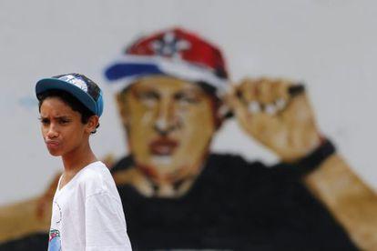 Un joven del barrio caraqueño de Petare delante de un grafiti de Hugo Chávez, ataviado con indumentaria de rapero.