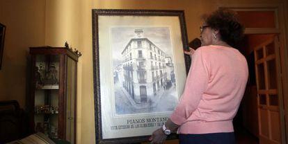 Una vecina muestra una lámina del edificio de Pianos Montano vendido por Afal.