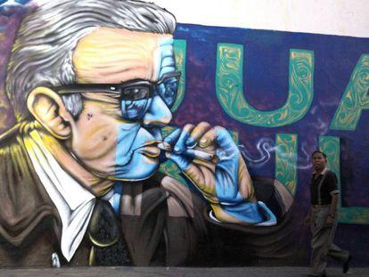 Un hombre pasea frente a un mural con una imagen de Juan Rulfo en Tuxcacuesco (México).