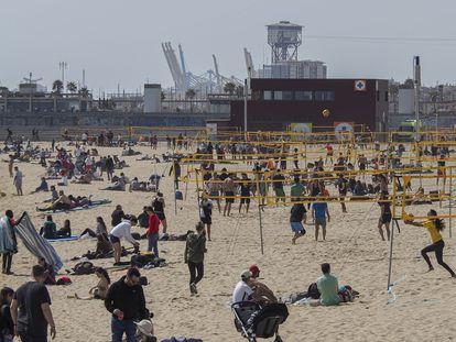 Aficionados al voley playa ocupan la mayoría del espacio en la playa del Bogatell de Barcelona, este sábado.