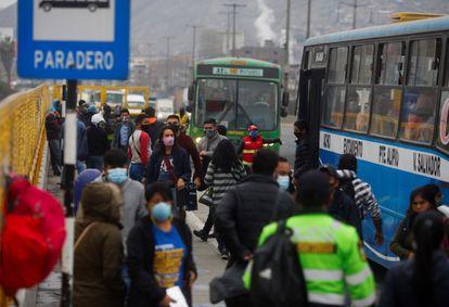 Varias personas pasan frente a una parada de autobuses en Lima (Perú).