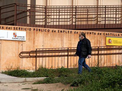 Un hombre con mascarilla pasa ante la entrada de la oficina del Servicio Público de Empleo de la Junta de Castilla y León en Ávila.
