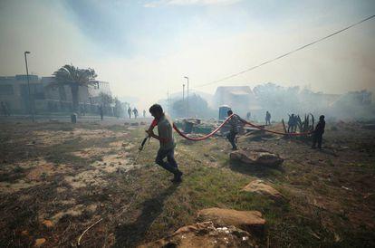 Residentes y bomberos voluntarios luchan por contener un incendio avivado por fuertes vientos en las laderas de la Montaña de la Mesa en Ciudad del Cabo, Sudáfrica.