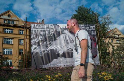 Un hombre pasa delante de una de las famosas imágenes que Koudelka tomó en 1968 situada en una calle de Praga.