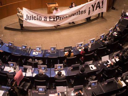 Legisladores del PAN y Morena sacaron pancartas durante la sesión sobre la consulta a los expresidentes en la Cámara Alta.